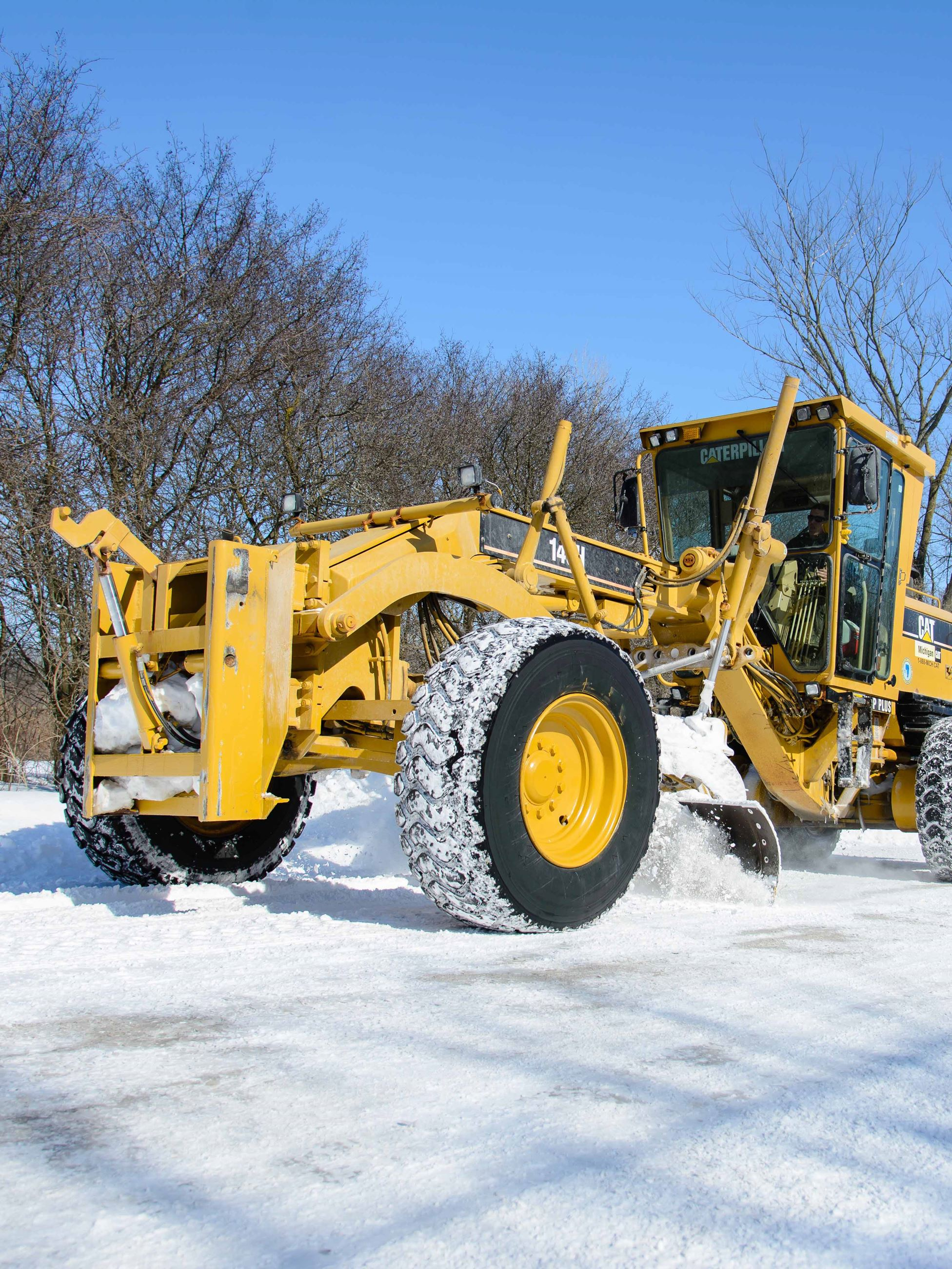 grader plowing snow